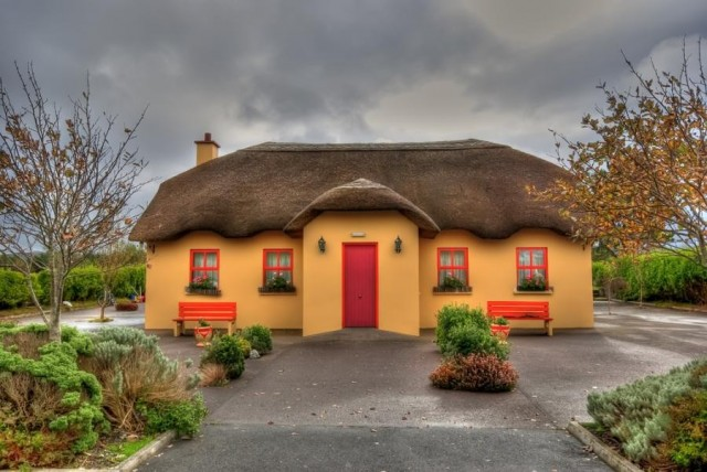 Colorful Irish cottage with thatched roof.